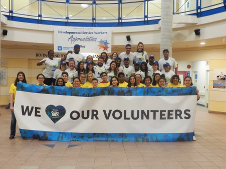 """A group shot of a bunch of young people holding up a sign that reads """"We love our volunteers"""""""