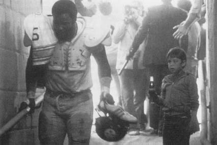 "Football player ""Mean"" Joe Green appearing in a now-famous Coca-Cola telvision commercial. Reproduced by permission of AP/Wide World Photos."