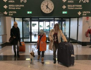 family with dog in Milan Malpensa airport carrying luggage