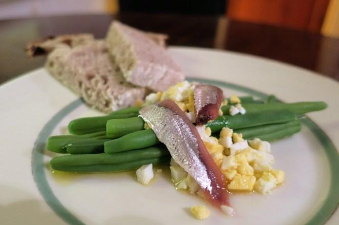 Haricotsvert med et kogt hakket æg og ansjoser.