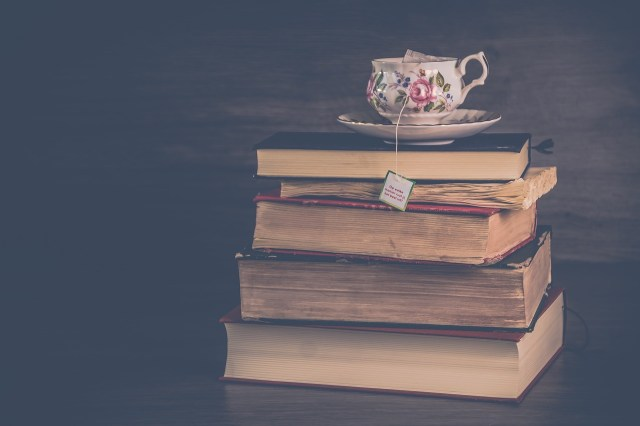 carti stivuite cu o ceasca de ceai in varf