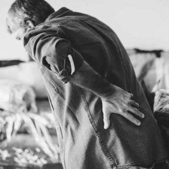 man bent over with low back pain with coronavirus