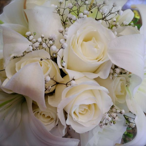 An arrangement of white roses with mixture of lily.