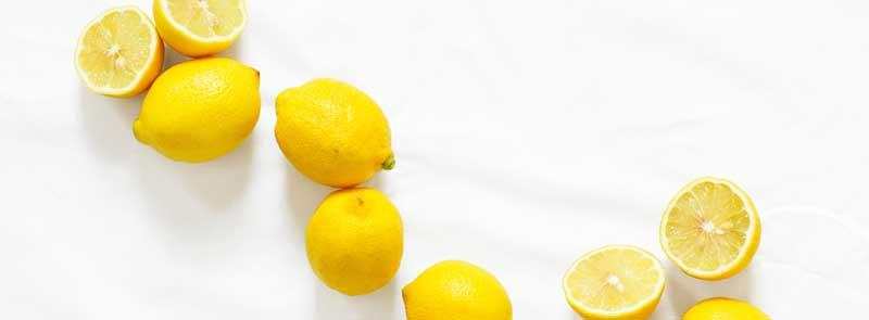 Photographie de citrons entiers et tranchés sur fond blanc