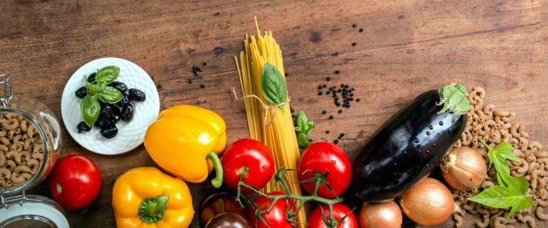 Photos de légumes et de pâtes sur une table en bois : le régime végétarien est positif pur le plus grand bonheur des végétariens
