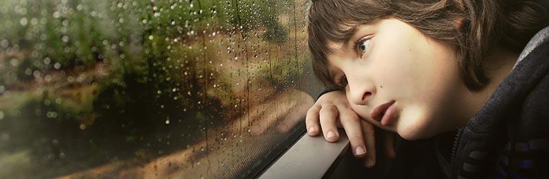 Photographie d'un enfant fatigué, la tête posée sur ses mains, regardant la pluie tomber à travers la fenêtre d'un train, pour illustrer les carences en fer et la fatigue de l'anémie suite au manque d'aliments riches en fer.