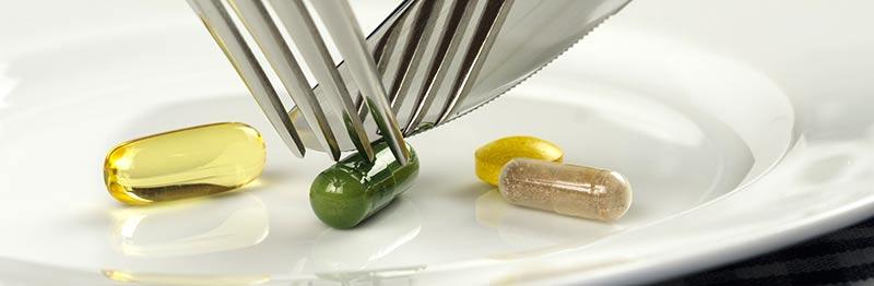 Photographie couleur de 4 pilules de compléments alimentaires de couleur jaune, transparente, beige et verte, posées dans une assiette blanche, avec quelqu'un essayant de les couper pour les manger à l'aide d'une fourchette et d'un couteau. Les compléments alimentaires sont-ils dangereux ? Voici quelques éléments de réponse avec le laboratoire Shavi.