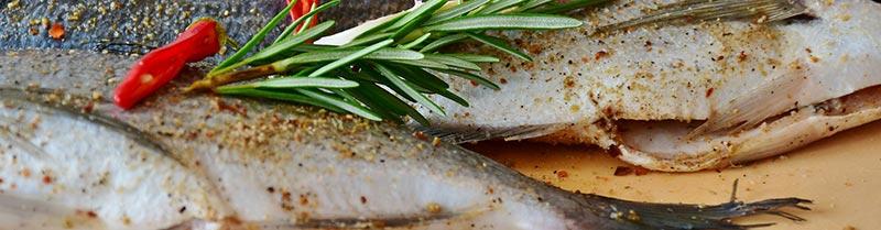 Photographie de poissons en gros plan sur un plan de travail avant leur cuisson, pour illustrer que le poisson est un aliment riche en fer.