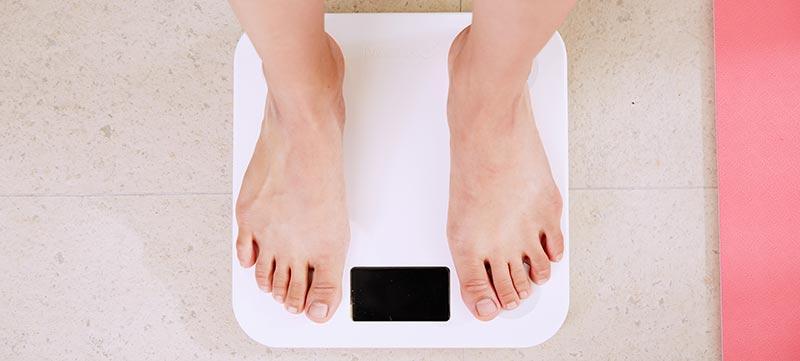 Photographie des pieds d'une femme sur une balance pour mesurer son poids dans le cadre d'un régime amincissant pour perdre du poids.