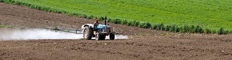 Photographie d'un agriculteur répandant des pesticides sur son champ nu à l'aide de son tracteur, ce qui est interdit pour les aliments bio