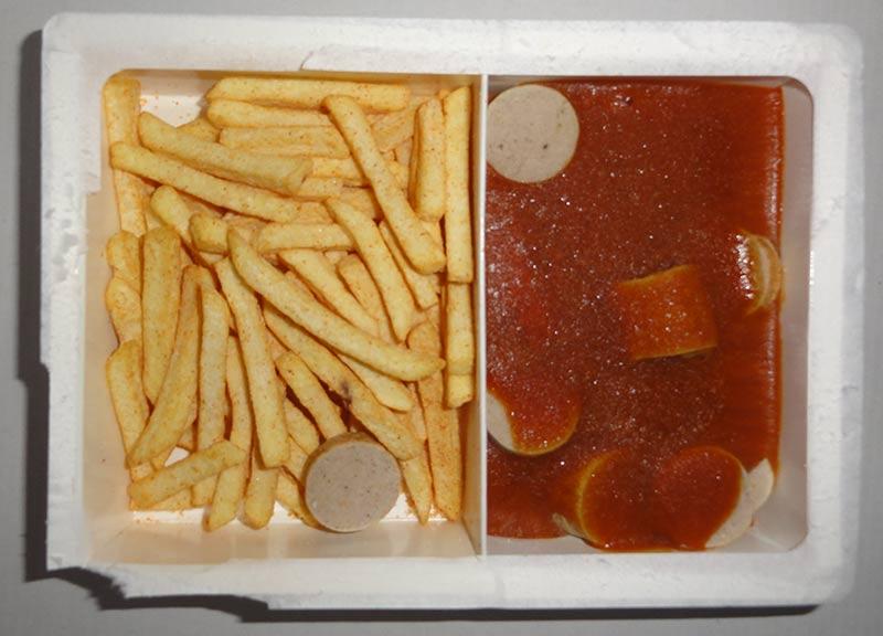 Photographie en gros plan d'un plat tout-prêt industriel avec frites, saucisse végétarienne et sauce : les aliments bio ne sont pas meilleurs pour la santé !