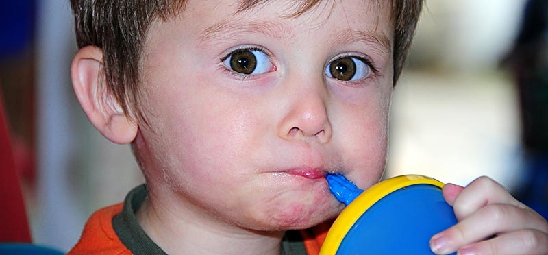 Photographie d'un enfant blanc en train de boire à une gourde bleue. L'éducation alimentaire permet de prémunir de l'obésité infantile.