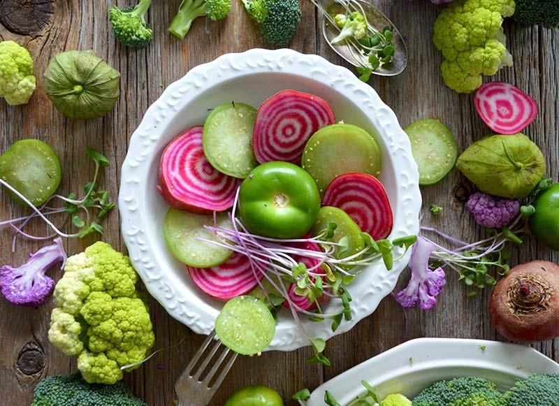 Minéraux, acides aminés, acides gras, tous les oligo-éléments essentiels pour la santé présents dans cette photographie d'une assiette remplie de légumes frais et crus (betterave, poivron, chou-fleur, germes, concombres).