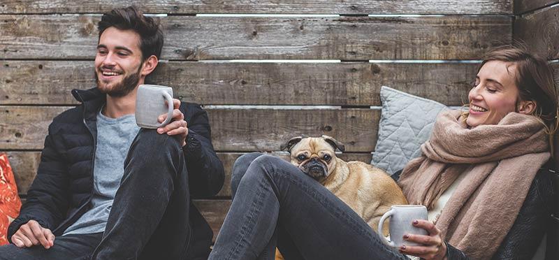 Photo d'un homme, d'une femme et d'un chien buvant un café sur une terrasse