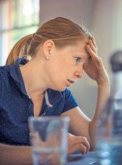 Photographie d'une femme stressée et fatiguée se tenant la tête des les mains en raison d'un manque de magnésium, une carence nutritionnelle causée par un excès de café et de caféine, qui favorise la fuite de magnésium de l'organisme.