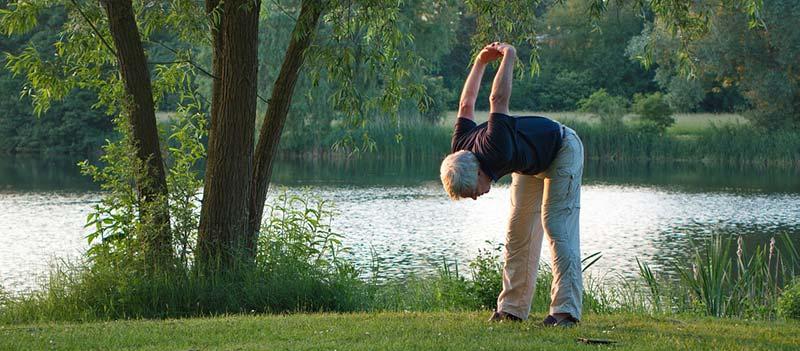 Photographie effectuant des exercices de yoga en plein air afin de lutter contre l'arthrose et retrouver ses mouvements et sa souplesse. Mangez mieux, bougez plus pour dire Stop Arthrose !
