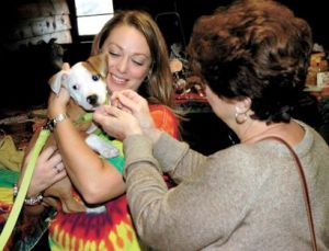 Renee Earl, left,  fundraising committee chairperson and media relations for the Regional Animal Shelter holds a dog named Stryker as her mom Pat Earl of Amsterdam reaches out to pet him during the annual Wookstock event at Robin's Nest in Broadalbin on 9/14.  This event benefits the Regional Animal Shelter. The Leader-Herald/Bill Trojan