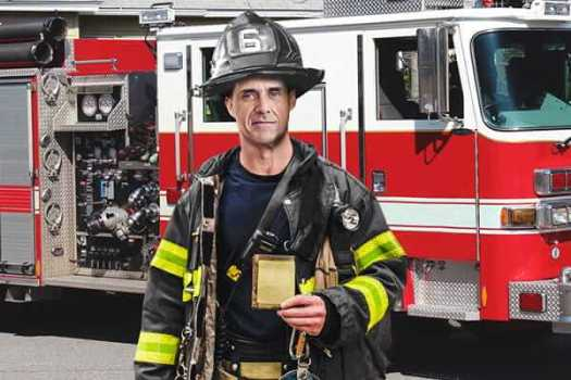 mike banner the creator of okinawa flat belly tonic wearing a firefighter's suit and accessories such as a protective helmet and a firetruck is in the background