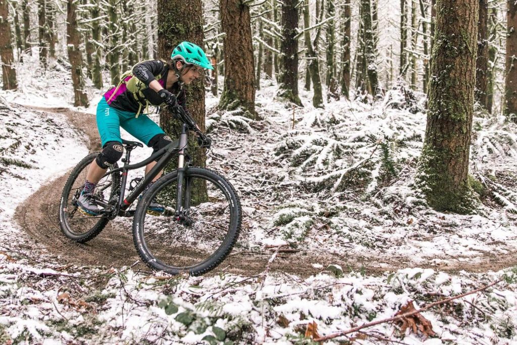 Woman cornering on a mountain bike in snow