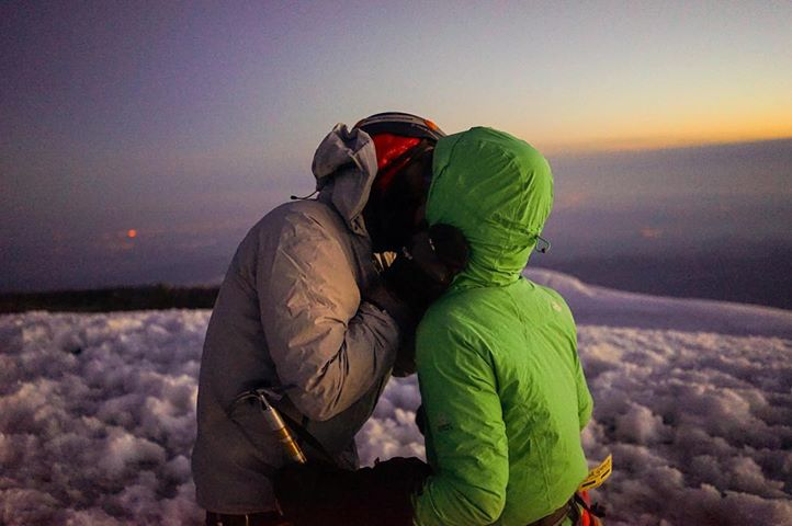 Couple kisses at the top of Mount Rainier.
