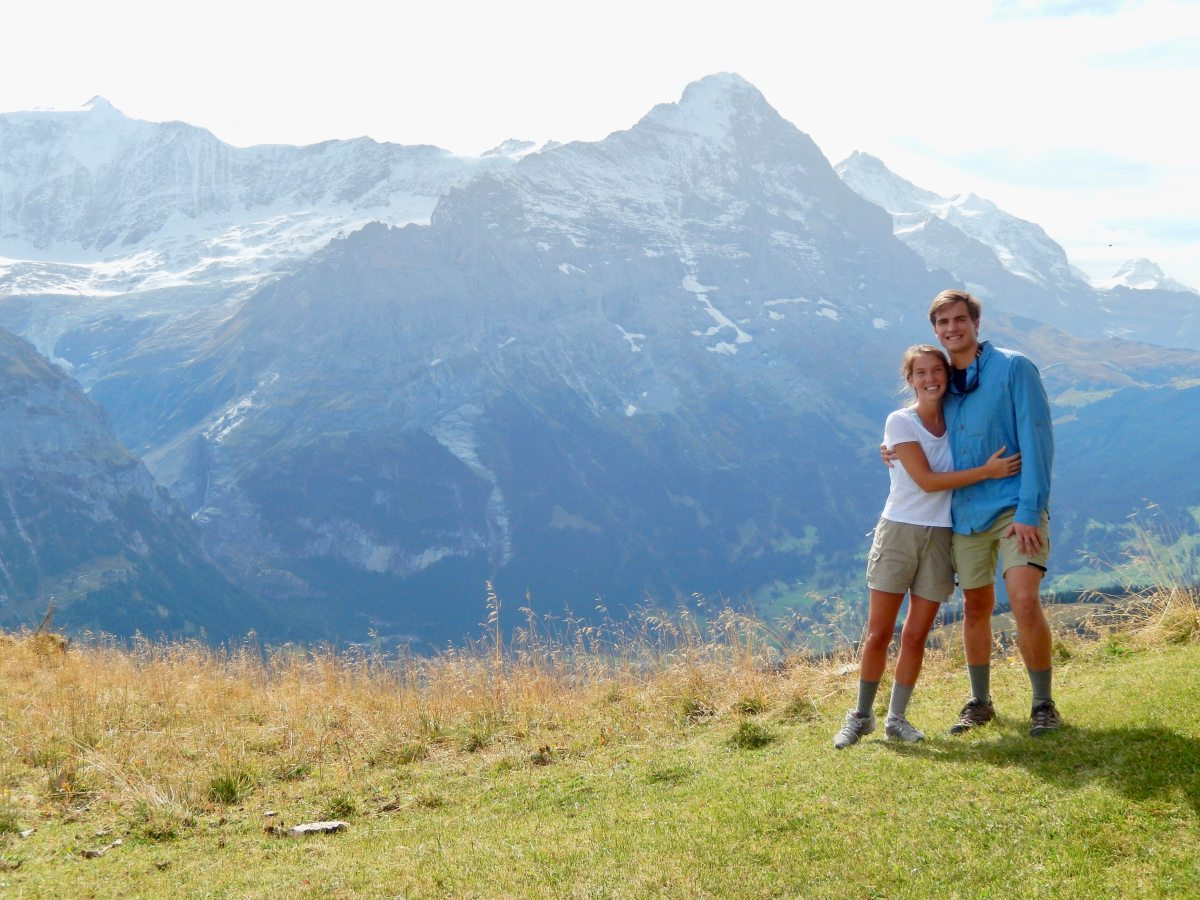 The couple hugs with a backdrop of tall, snow topped mountains.