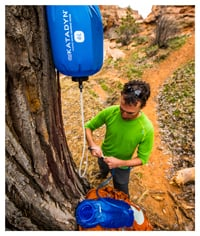 Seorang kemping menggantungkan filter gravitasi dari pohon