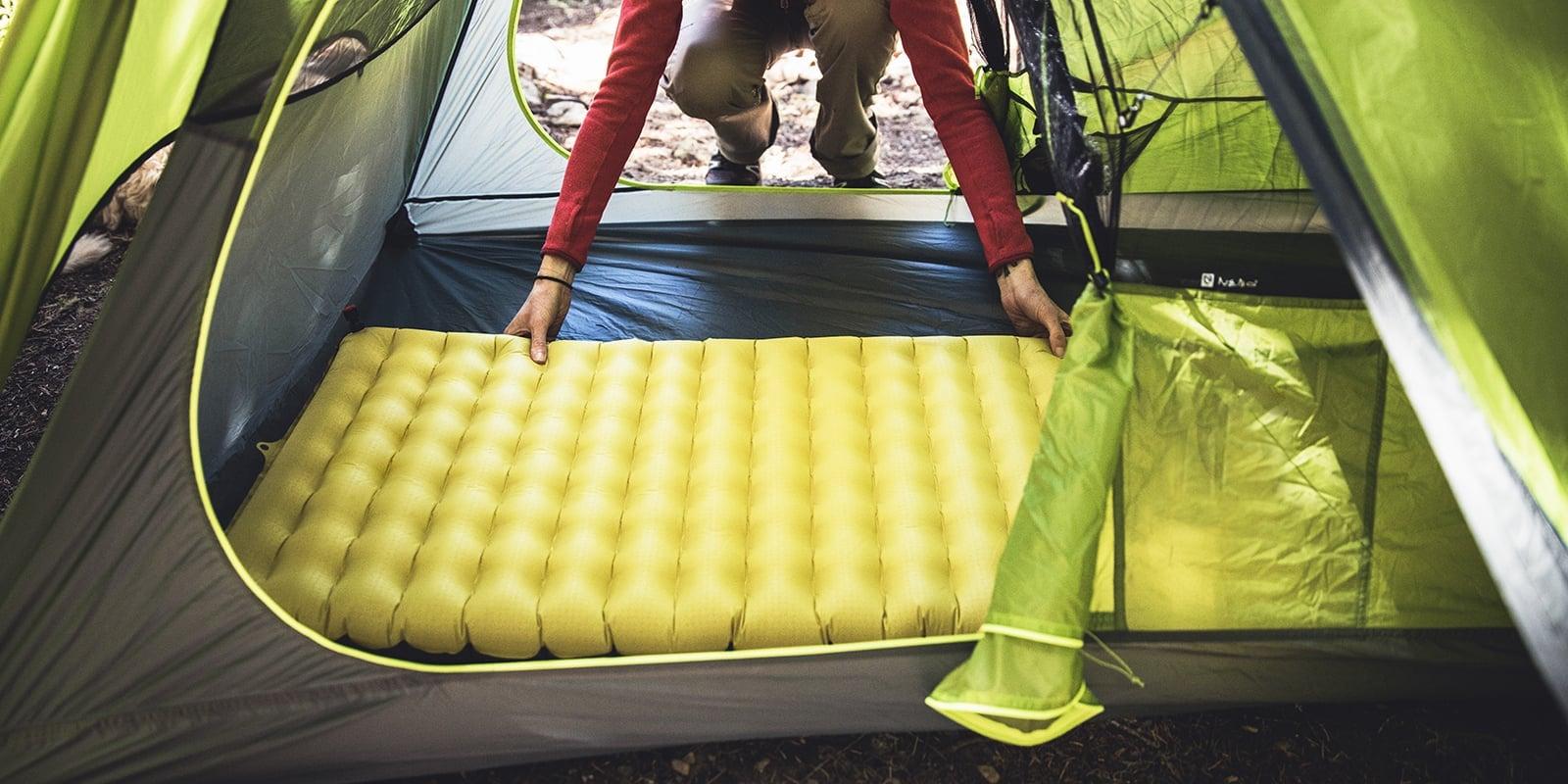 Camper meletakkan alas tidur ke dalam tenda