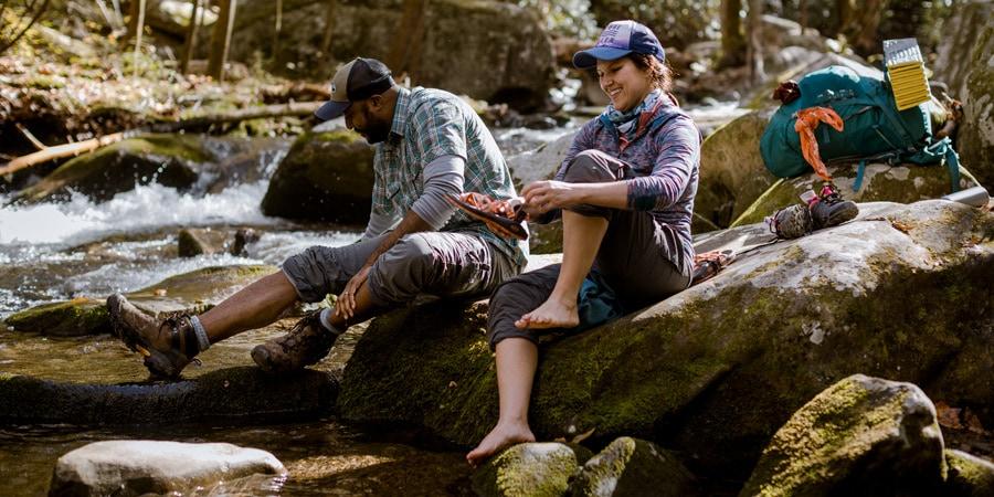 Dua backpacker bersantai di dekat sungai