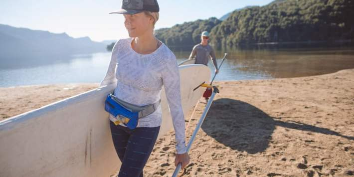 Woman carrying SUP stand up paddle board