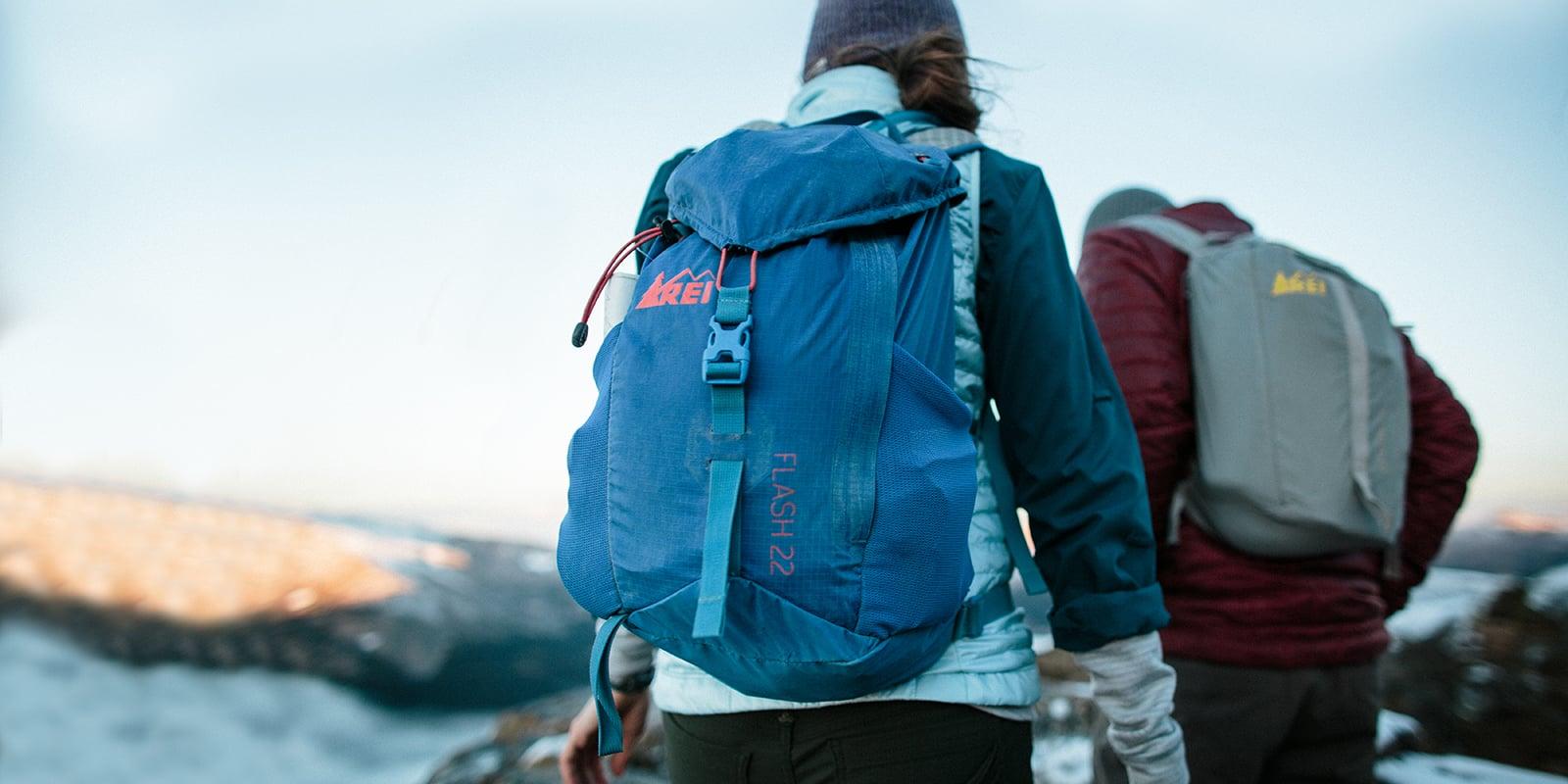 Dua orang mendaki jalan setapak di punggung bukit dengan menggunakan tas punggung REI Flash