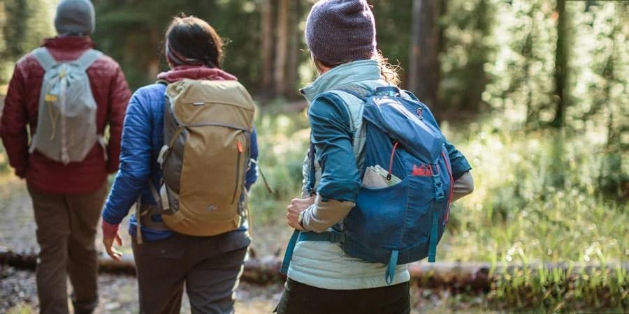 tiga pendaki di jalan setapak dengan tas punggung mereka