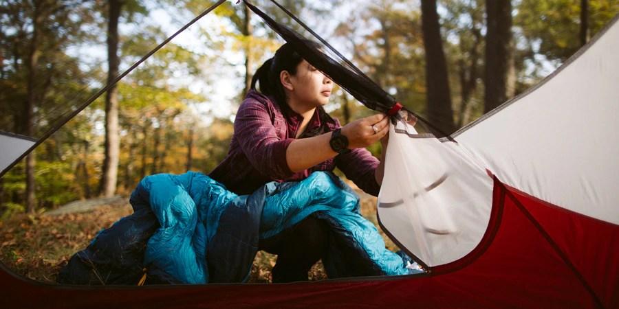 Seorang wanita mendirikan tendanya saat dalam perjalanan backpacking