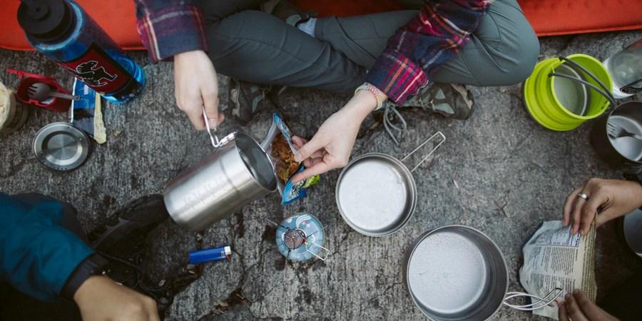 Seorang backpacker menyiapkan makanan dengan menambahkan air mendidih ke makanan kering beku