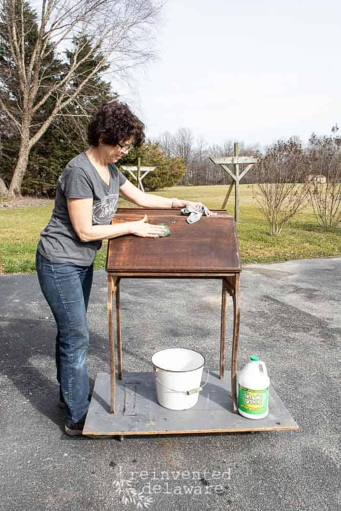 lady scrubbing an antique fold down secretary desk