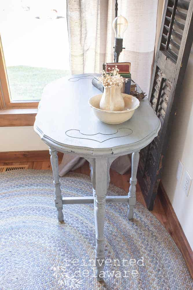 This scalloped edge side table started out pretty dark.  I loved the shape of it and I knew that painting the whole piece would bring out the details. #vintagefurniture #furnituremakeover #mmsmilkpaint
