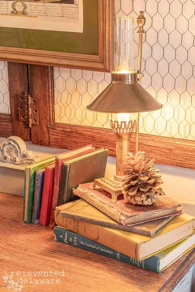small brass lamp sitting on stack of vintage books with gold pinecone next to lamp all on top of vintage buffet