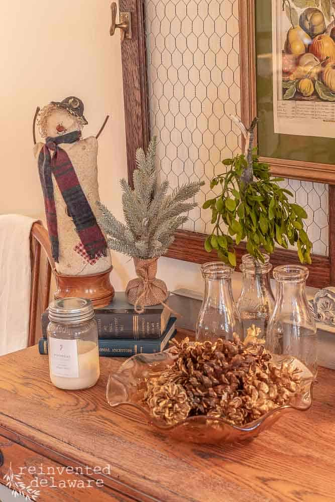 close up of snowman, mistletoe, small Christmas tree and pinecones in a bowl all sitting on top of vintage buffet
