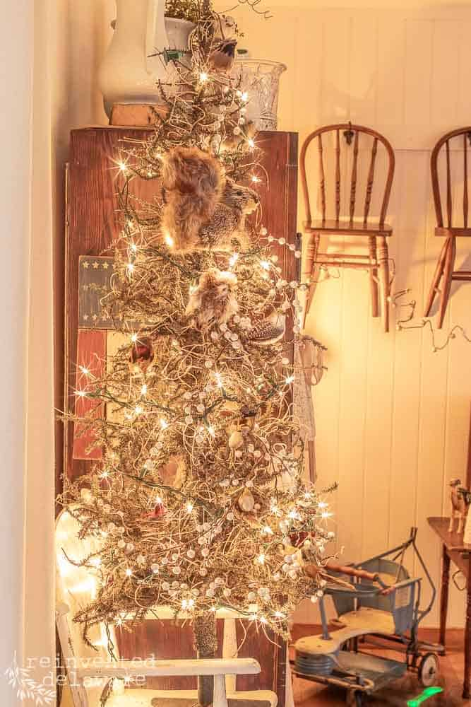 Christmas tree with woodland creature ornaments. tree is on a vintage highchair