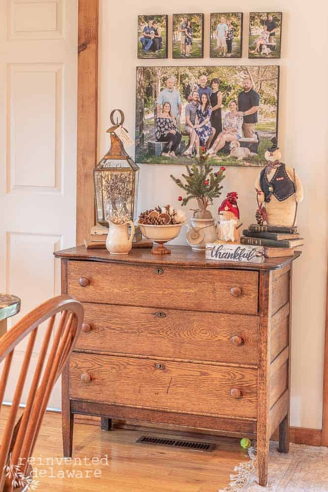 antique dresser with   Christmas decor on top including handmade snowmen, small Christmas tree, ironstone, brass and copper lantern. Family photos hanging above dresser