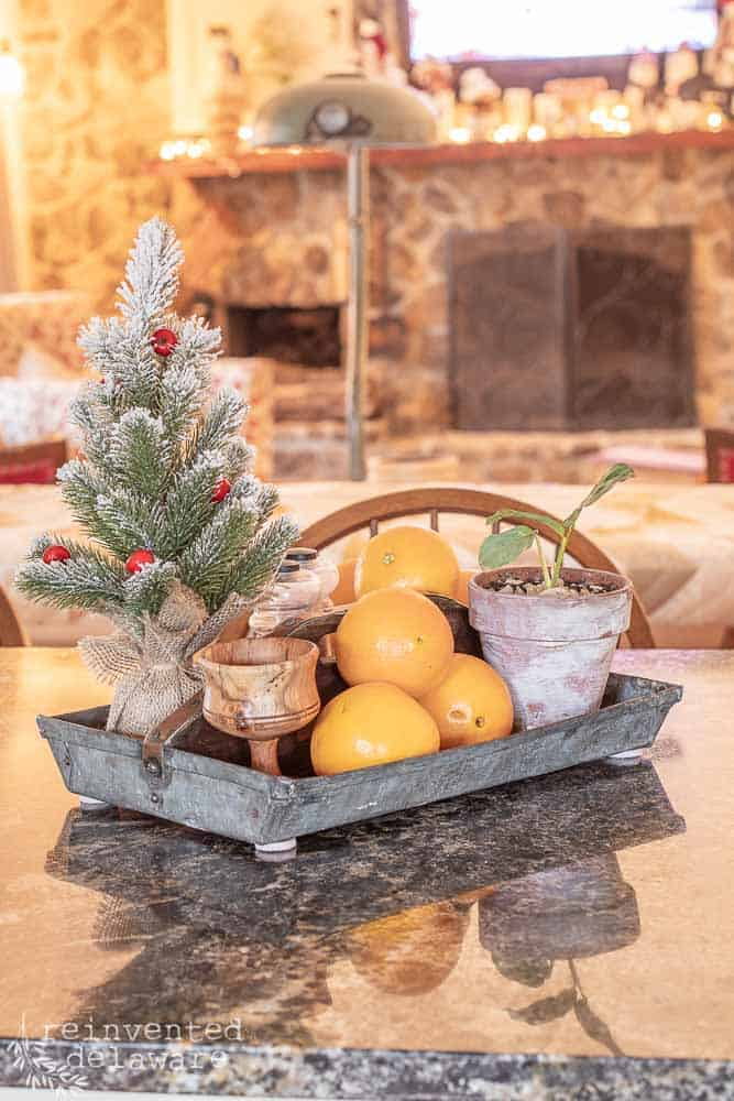 vintage metal tool caddy with small Christmas tree, oranges, salt & pepper shakers used as kitchen island centerpiece