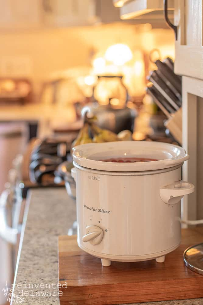 small crock pot sitting on kitchen counter filled with simmering potpourri