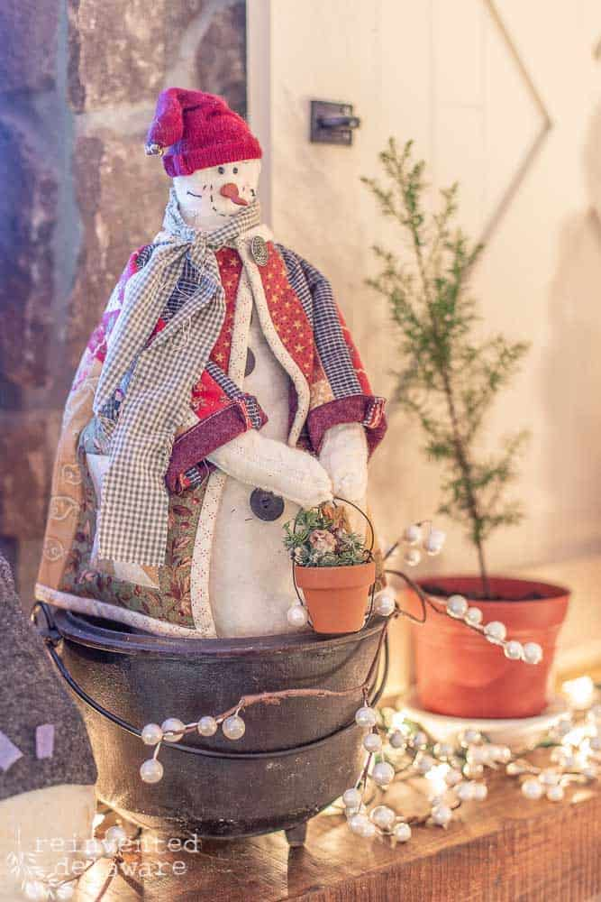handmade snowman in quilted jacket holding terra cotta pot of pine cones