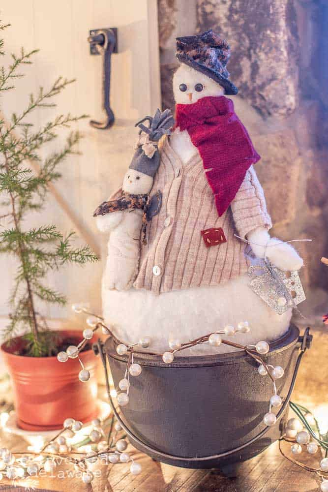 handmade snowman sitting on top of mantle in a vintage cast iron pot. snowman is dressed in upcycle seater hat and jacket