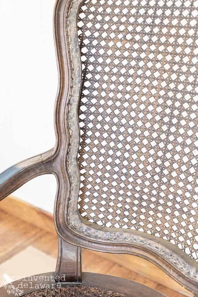 close up of back section of caned chair with caning removed first step in repairing furniture