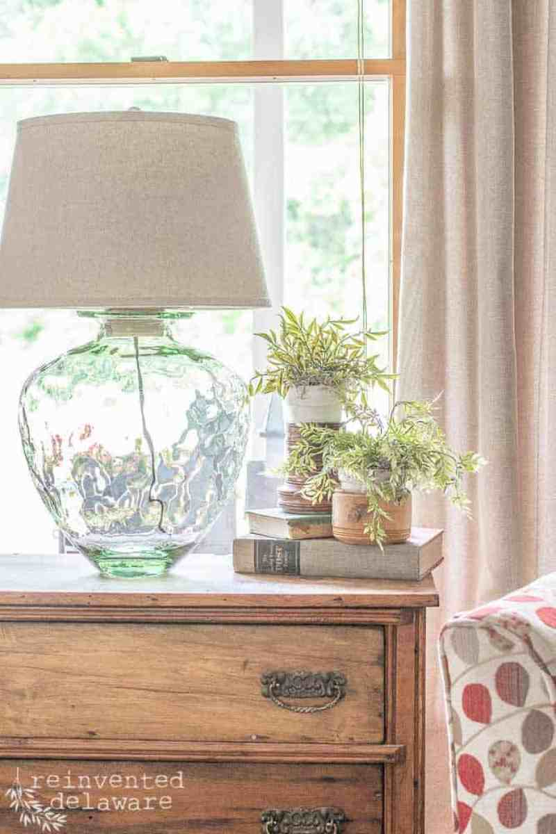 glass jar upcycle lamp project finished and sitting on top of washstand with faux plants and vintage books