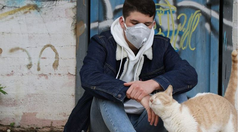 Mann mit Katze und Mundschutz