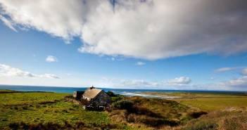 Ein typisches Bild für Irlands Wetter: Ein Haus an der Küste inmitten grüner Hügel. Am Himmel ziehen Regenwolken auf und wechseln sich mit der Sonne ab.