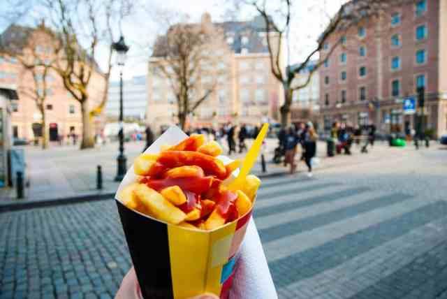Belgiske pommes fritter i forgrunden og gadeliv i baggrunden.
