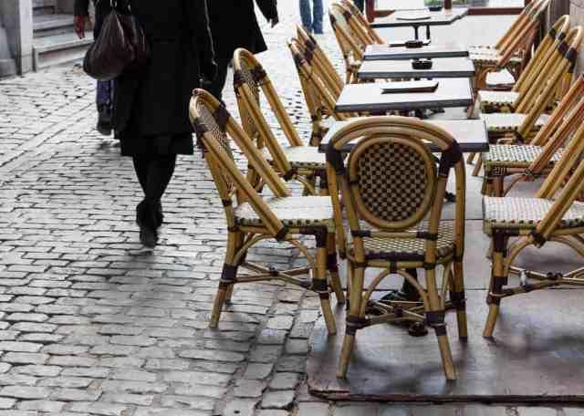 Caféborde- og stole ved brostensbelagt gade i Bruxelles. Gående personer i baggrunden.