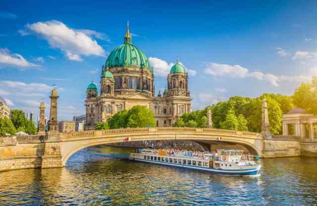 Udsigt over Berliner Dom på Museumsøen med bro og turistbåd i forgrunden